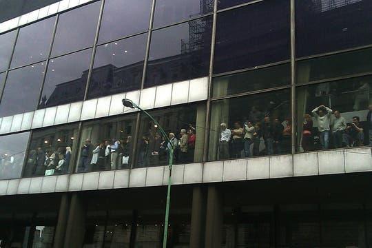 Trabajadores de la Bolsa de Comercio observan el paso del cortejo que lleva a Néstor Kirchner. Foto: LA NACION / Pablo Martín Fernández