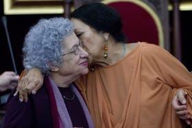 La escritora argentina Griselda Gambaro (i) recibe un beso de de la viuda de Atahualpa del Cioppo