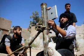 Un rebelde sirio calibra un mortero con la ayuda de tecnología estadounidense, a través de un iPad