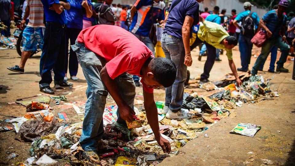 Un chico busca comida afuera de uno de los locales que fueron saqueados anoche. Foto: AFP / Ronaldo Schemidt