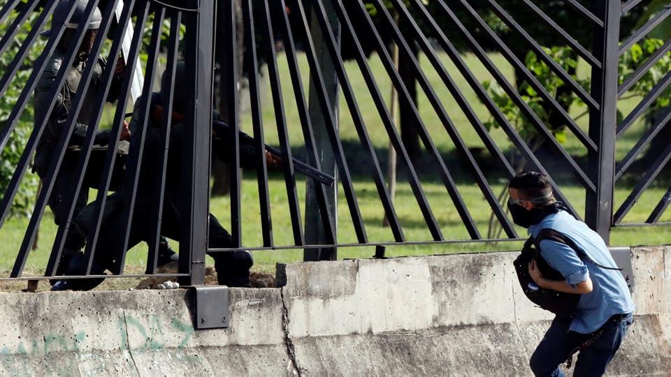 El momento en el que un policía antidisturbios le dispara al manifestante en el cerco de una base aérea en Caracas. Foto: Reuters / Carlos Garcia Rawlins