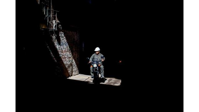 Un obrero de construcción anda en moto a través de la Villa
