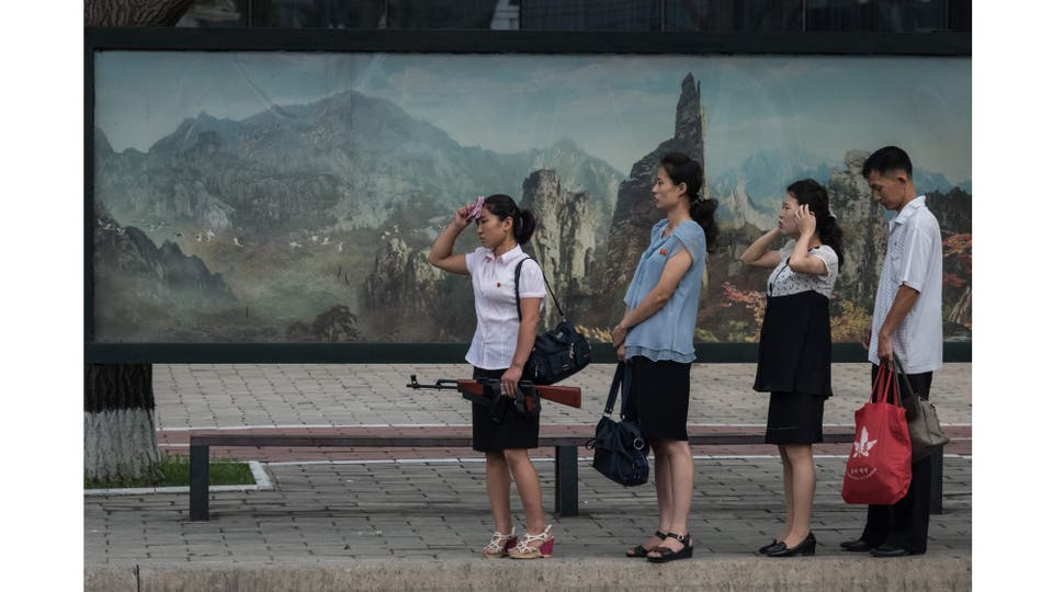 Una mujer sostiene un rifle de juguete mientras espera junto a otras personas el autobus en Pyongyang, 29 de julio 2017
