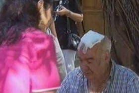 Una de las víctimas del asalto es asistida por una enfermera en la puerta de la Parroquia