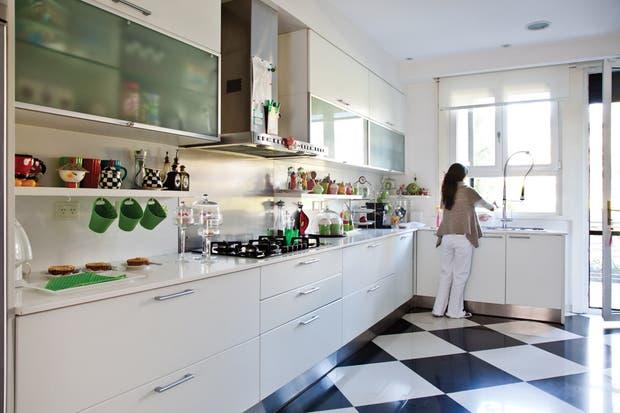 Amplia y luminosa, la cocina integra el área de la terraza y la parrilla con el mismo piso de porcelanato de 60x60 (SBG). El mueble en forma de L con mesada de Silestone fue realizado por un carpintero; es totalmente blanco, a excepción de los herrajes, la alzada y el zócalo de acero inoxidable..