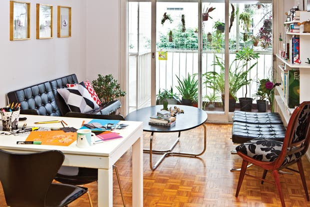 En la pared tras el sillón Barcelona, imágenes de obras e Hella Jongerius con marcos dorados a la hoja. Sobre la mesita oval negra (Neoda), figuras de madera pintadas a mano por Laura..