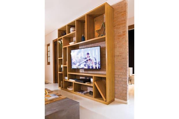 Tras tirar todas las divisiones, se reconstruyó la pared entre el pasillo y el living utilizando ladrillos antiguos rescatados de la obra, que se dejaron a la vista como fondo de la biblioteca. El mueble que contiene la TV también se hizo de guatambú para reforzar la unidad de este espacio de usos m.  /Santiago Ciuffo