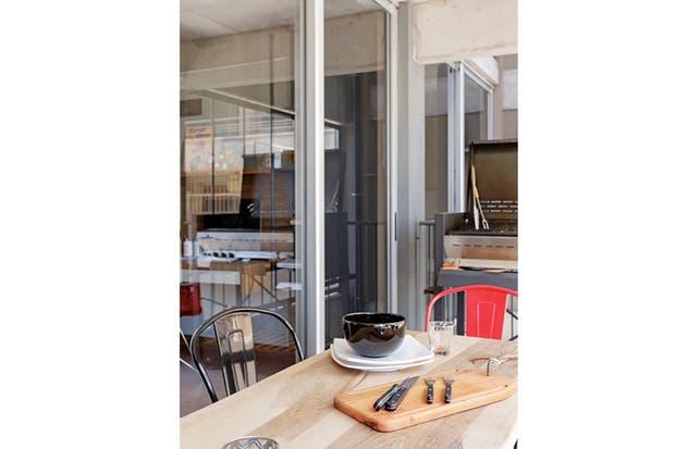 Equipado para recibir amigos, con parrilla (Diwar) y mesa angosta con tapa de guayubira encerada: un diseño propio combinado con sillas 'Tolix'.  Foto:Living /Daniel Karp