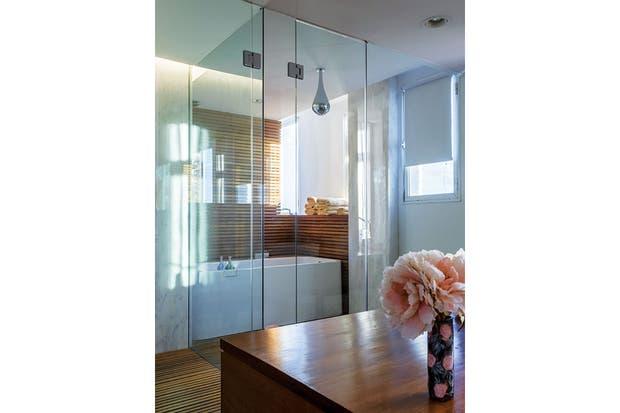 . La ducha 'Gota' de Gessi (Barugel), también tiene similar origen: Jackie la vio en el hotel Vik de José Ignacio. La zona húmeda del baño, dividida por una mampara de vidrio, se resolvió con piso de varillas de madera, que se continúan también en la pared.  Foto:Living /Daniel Karp