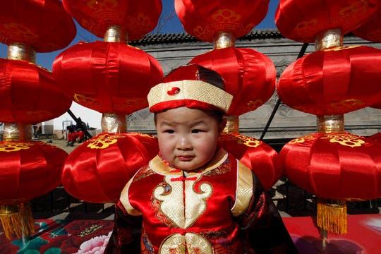 Un niño vestido con un traje tradicional chino se encuentra delante de las lámparas en un templo para celebrar el Año Nuevo Lunar en Beijing. Foto: Reuters