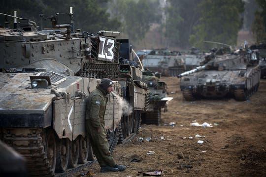 Un soldado israelí descansa mientras espera para una fuerte ofensiva terrestre. Foto: AFP
