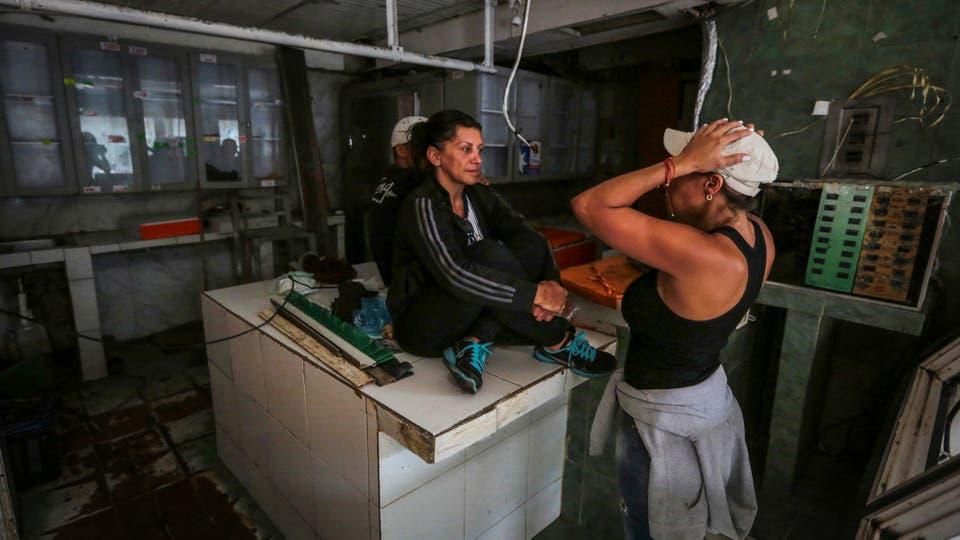 La dueña de una carnicería, Liliana Altuna, habla con una empleada dentro de su tienda que fue saqueada anoche, en el barrio El Valle de Caracas. Foto: Reuters / Fernando Llano