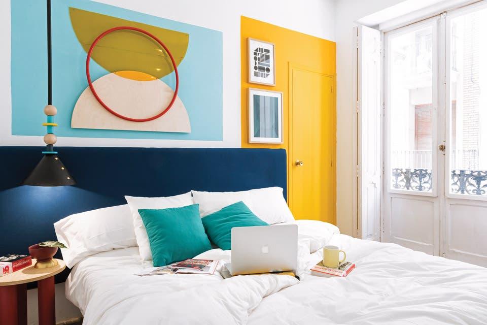 """La puerta en amarillo ya hubiera sido un desafío para muchos. ¿Y llevarlo más allá del marco para que respete la proporción del rectángulo celeste y """"sostenga"""" los cuadros? En cada caso, el respaldo es verdadero apoyo de un sueño.  /Gentileza Estudio Masquespacio"""