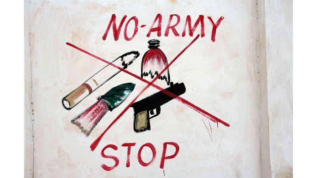Una ilustración que prohíbe armas, botellas rotas, cigarrillos y armas en una pared de un estadio en el distrito de Hodan