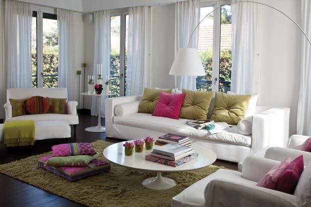 El living es casi íntegramente blanco, con cortinas de voile, confortables sillones con fundas, una gran lámpara de pie tipo Twiggy y dos mesitas Tulip..