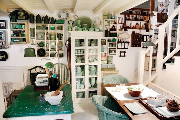 La gran mesa, con la tapa que evidencia su uso, y las sillas de ratán en verde inglés. Parece una auténtica cocina de los años 30. En la escalera comienza el cambio de tono..