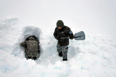 El trabajo en equipo es una de las claves: en este caso, mientras un gendarme cava dentro de la futura cueva, otro va retirando la nieve que saca y la tira más lejos.