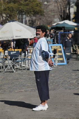 """Escolástico Berto Méndez dice ser el doble oficial de Maradona. Atiende todos los días en su """"despacho"""" de Caminito, una foto con él, se cotiza $ 50"""