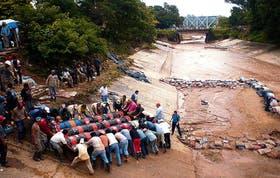 Empleados de la Municipalidad de Tartagal trabajan en las defensas del río homónimo, donde la crecida socavó los terrenos circundantes
