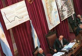 Carlos Ruckauf observa los mapas desplegados en el Senado mientras escucha los discursos