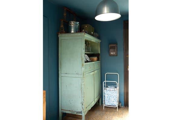 Junto al mueble de campo antiguo está el changuito de compras y una bolsa plegable eco..