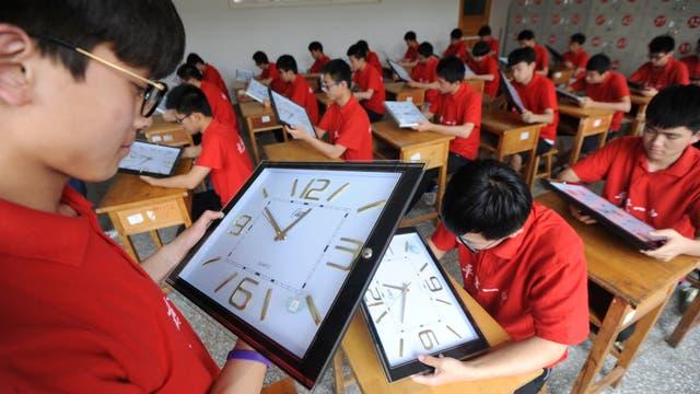 Profesores calibran los relojes de las aulas donde los alumnos rendirán los exámenes