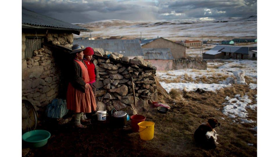 Rosa Carcabusto (29) y su hija María Luque (13), cocinan afuera de su casa a más de 5000 metros de altura en la localidad de Puno. Es invierno y las temperaturas llegan hasta 20° bajo cero. Perú, 9 de julio 2016. Foto: Rodrigo Abd