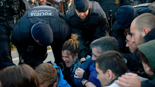 Policías regionales de Cataluña (Mossos d'Esquadra) arrastran piqueteros que bloquean la calle en la plaza de la Placa Cerda en Barcelona