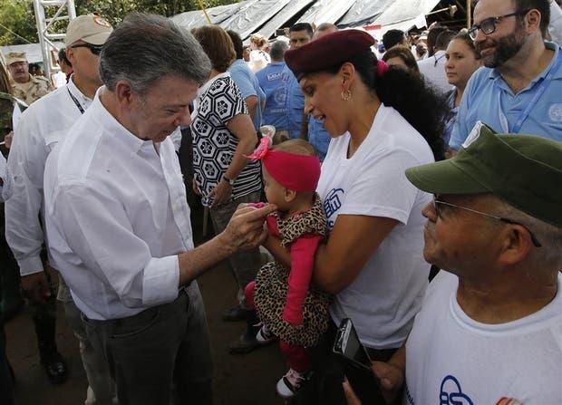 Santos saluda al bebe de un guerrillero en la ceremonia, en Mesetas