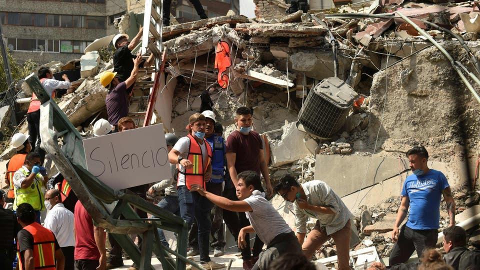 Los rescatistas piden silencio para poder escuchar los pedidos de auxilio bajo los escombros. Foto: AFP