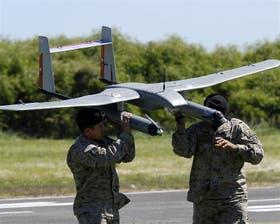 Dos soldados sujetan a Láscar, el primer drone hecho en Chile