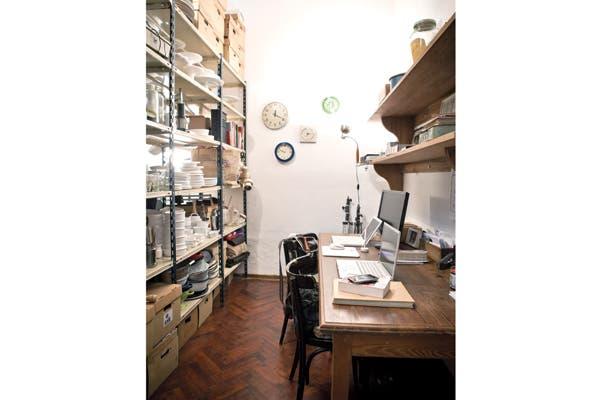 Como escritorio, una mesa de pinotea bien larga y una estantería de metal que sirve como archivo múltiple..