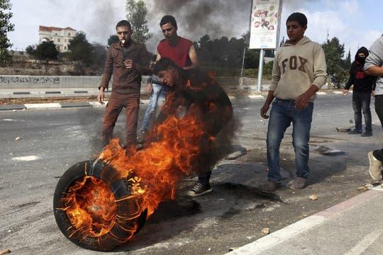 Varios palestinos prenden fuego a un neumático mientras participan en una manifestación contra Israel. Foto: EFE