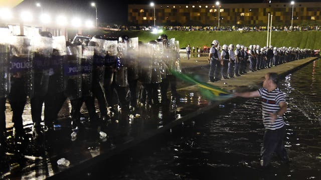 Un manifestante con una bandera se para frente a la policía que custodia el edificio del Congreso en Brasilia. Foto: AFP