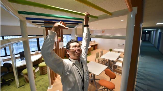 Un empleado de la empresa de fabricación de equipos eléctricos con sede en Tokio, Fujikura, mientras hace ejercicios en la sala de actividades de salud de la compañía.