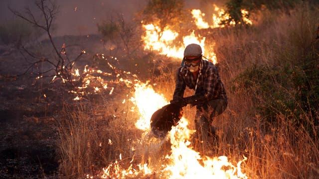 Un hombre apagando el fuego con un balde en las afueras de Sao Jose das Matas, cerca de Macao, Portugal