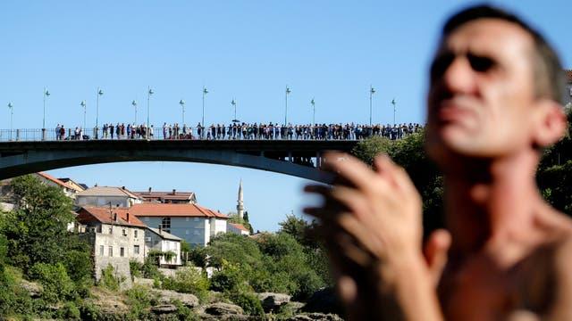 Espectadores miran a los competidores saltar del puente