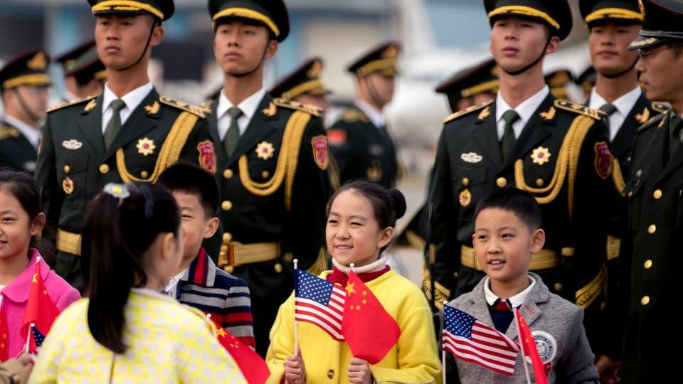 Soldados chinos y niños con banderas estadounidenses y chinas se alinean en la pista para saludar al presidente Donald Trump cuando llega al aeropuerto de Pekín. Foto: AP / Andrew Harnik