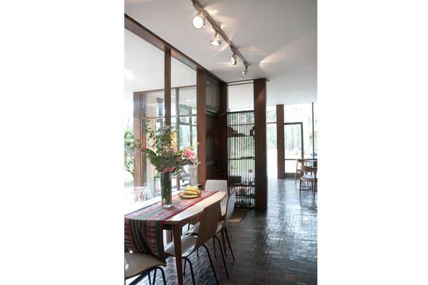 Además de por los materiales compartidos, la integración del interior con el exterior se logra, principalmente, por medio de los paneles de vidrio enmarcados en madera..