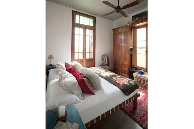 La cama del dormitorio principal está formada por dos catres con zunchos en las patas y un colchón hotelero para adaptarse a las visitas de Henry con su familia..