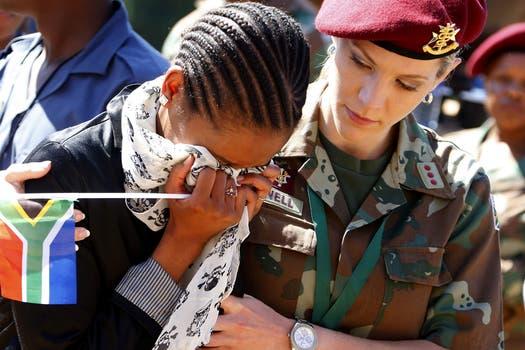 Una mujer llora tras el paso de la caravana que lleva a Mandela. Foto: EFE