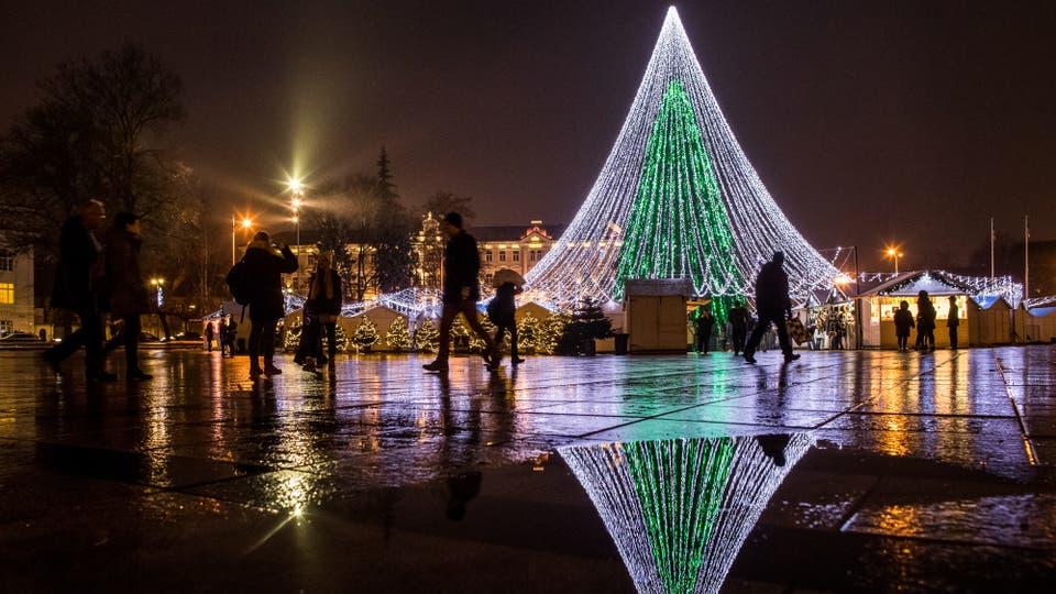 la gente camina delante del rbol de navidad iluminado en la plaza de la catedral en