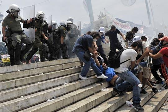 Los manifestantes ayudan a un compañero que sufrió un colapso durante los enfrentamientos. Foto: AFP