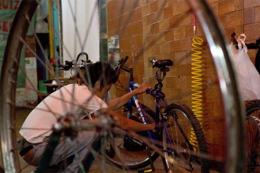 Un chico mira atento su bici, antes de empezar a arreglarla. Foto: LA NACION / Matías Aimar