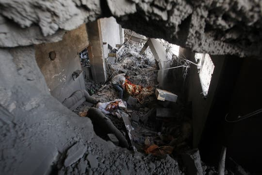 Palestinos inspeccionan los escombros de una casa destruida el pasado domingo por un ataque israelí en Gaza. Foto: AP