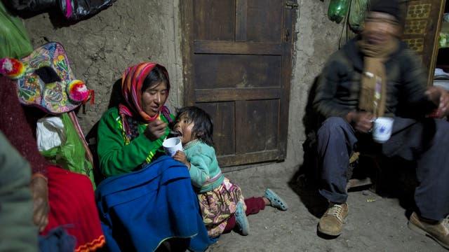 """María Ávila alimenta a su hija Shomara en la casa de adobe de su familia en Coata, una aldea en el costado del lago Titicaca, en la región de Puno, Perú. Avila se enojó mientras hablaba de la contaminación del lago. """"Mis antepasados han vivido aquí más de 500 años. Nunca han pasado por estas cosas """""""