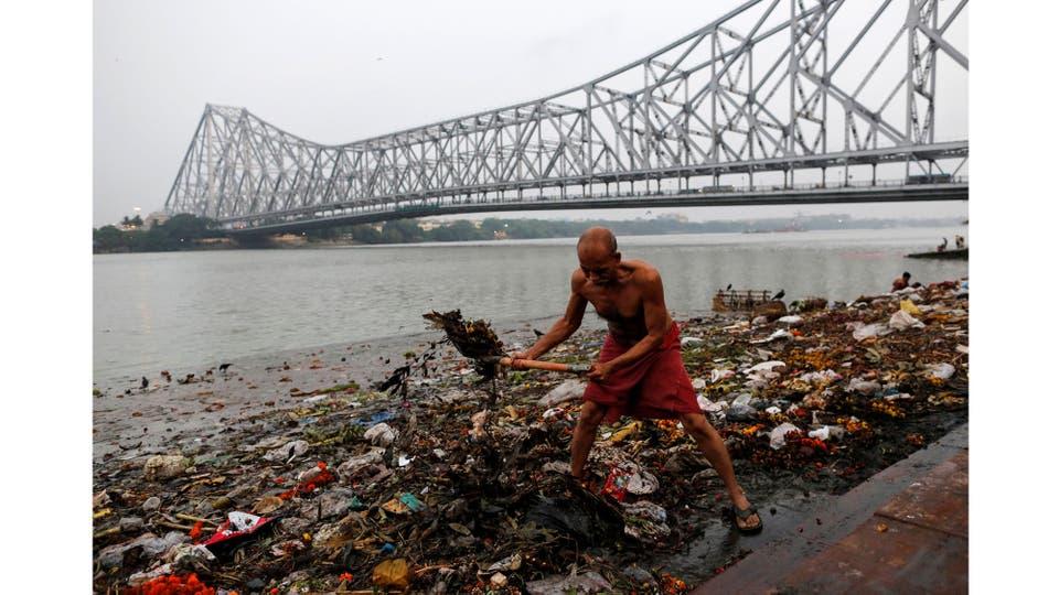 Un hombre limpia basura a lo largo de las orillas del río Ganges en Kolkata