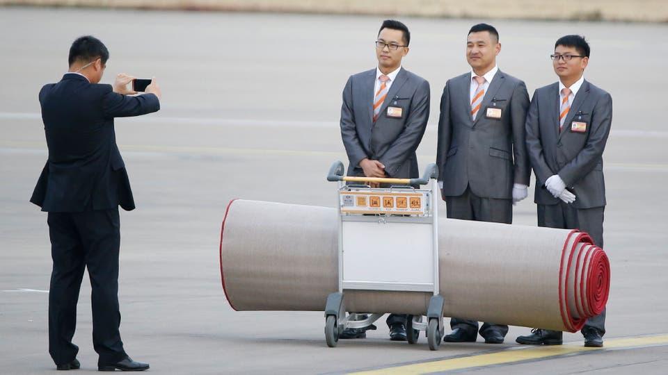 Miembros del staff toman una fotografía con la alfombra roja que sirvió para el arribo de Trump a China . Foto: AFP / Thomas Peter