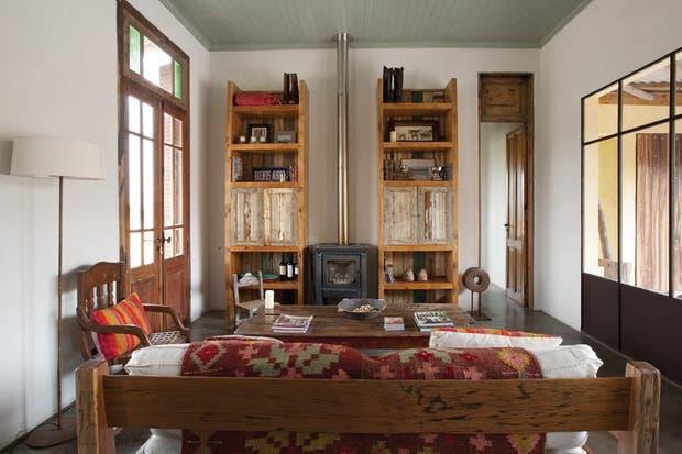 . El ambiente principal está armado en torno a una estufa a leña (Bosca) centrada entre dos bibliotecas de madera reciclada (El Chañar) un diseño de Marcela que acompaña la altura de las puertas..
