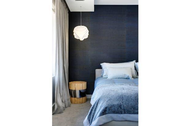 En el cuarto de huéspedes, pared entelada y lámpara colgante sobre una original mesa de luz: un haz de troncos unidos por una cintura de metal..